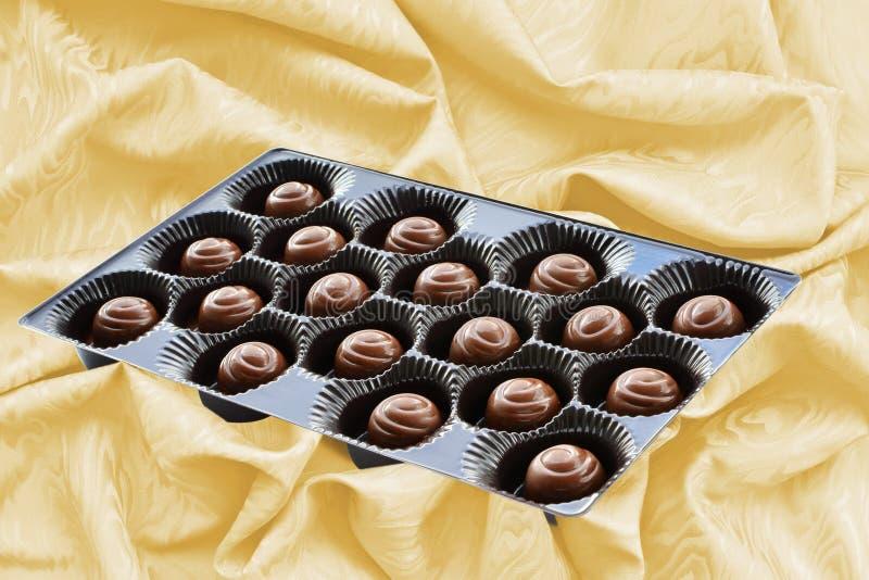 Czekoladowi cukierki w brązie boksują nad jedwabniczym tłem obraz stock