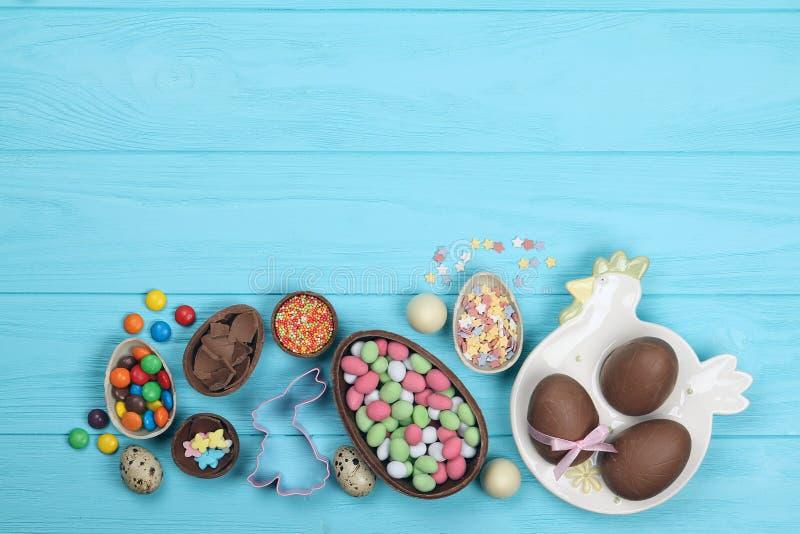 Czekoladowi Easter jajka, cukierki na błękitnym tle obrazy stock