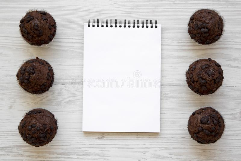 Czekoladowi muffins i pusty notepad na białej drewnianej powierzchni, zasięrzutny widok obraz royalty free