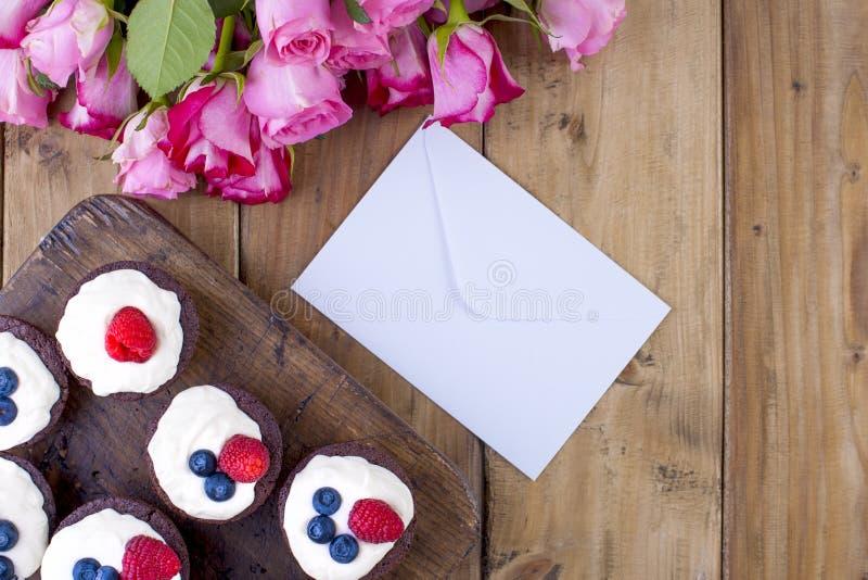 Czekoladowi muffins z, biała serowa śmietanka na brown drewnianej desce, i, Bukiet świeże różowe róże obrazy stock