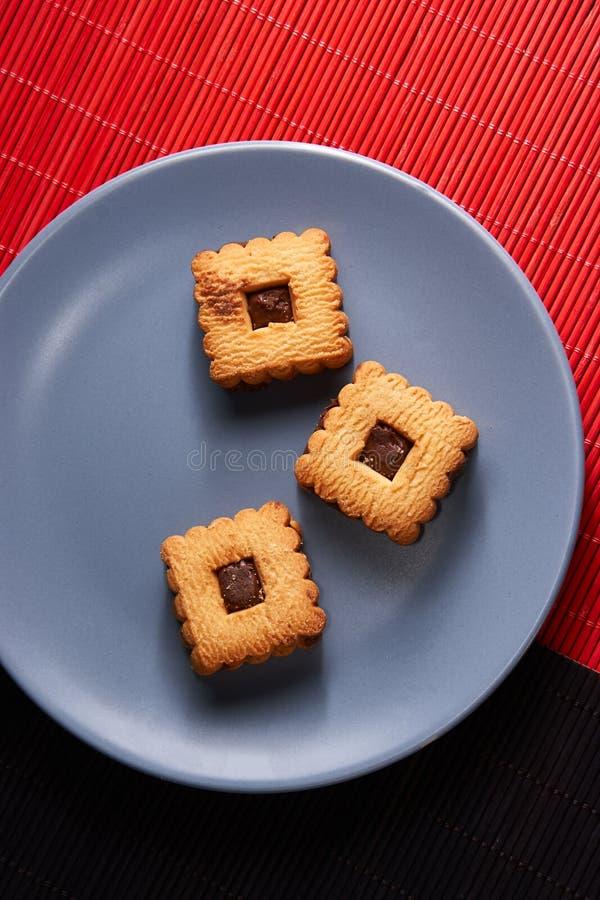 Czekoladowi piaska układu scalonego ciastka brogujący up na talerzu, przygotowywającym słuzyć na błękita talerzu zdjęcie stock