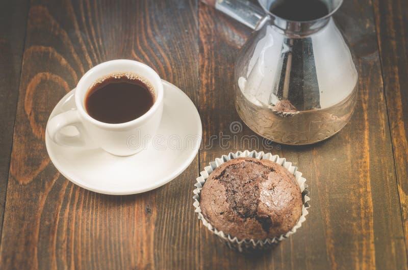 czekoladowi słodka bułeczka, biała filiżanka i turkowie,/czekoladowi słodka bułeczka, biała filiżanka i turkowie na drewnianym tl zdjęcie royalty free