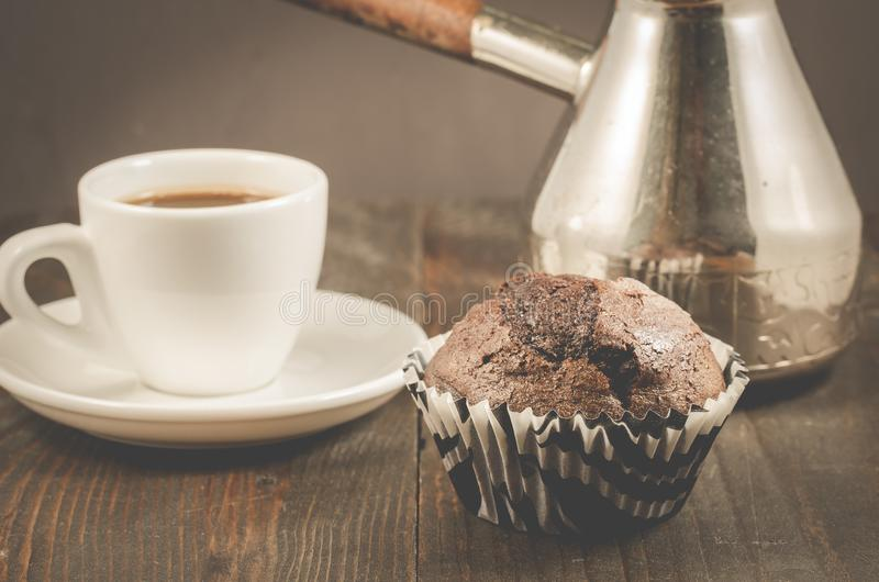 czekoladowi słodka bułeczka, filiżanka i turkowie,/czekoladowi słodka bułeczka, filiżanka i turkowie na drewnianym zmroku stole,  obraz royalty free