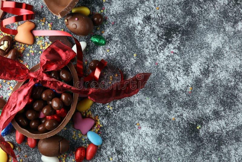 Czekoladowi Wielkanocni jajka z kolorów tasiemkowymi łękami na rocznika backgrou zdjęcia stock