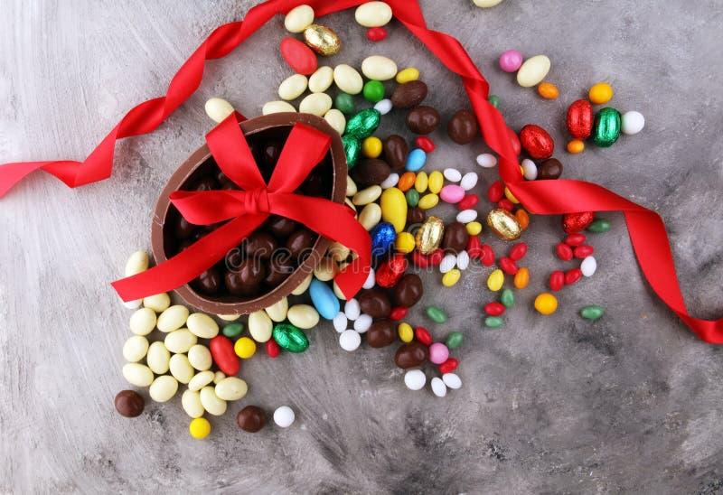 Czekoladowi Wielkanocni jajka z kolorów tasiemkowymi łękami na rocznika backgrou zdjęcia royalty free