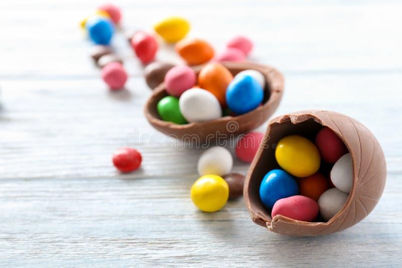 Czekoladowi Wielkanocni jajka z kolorowymi cukierkami na białym drewnianym tle zdjęcie royalty free