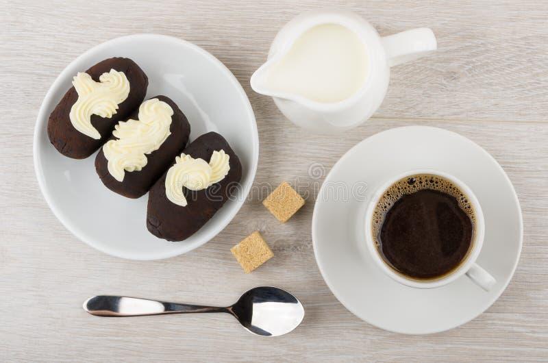 Czekoladowy ciastko zasycha z buttercream w spodeczku, dzbanka mleko, co zdjęcia royalty free