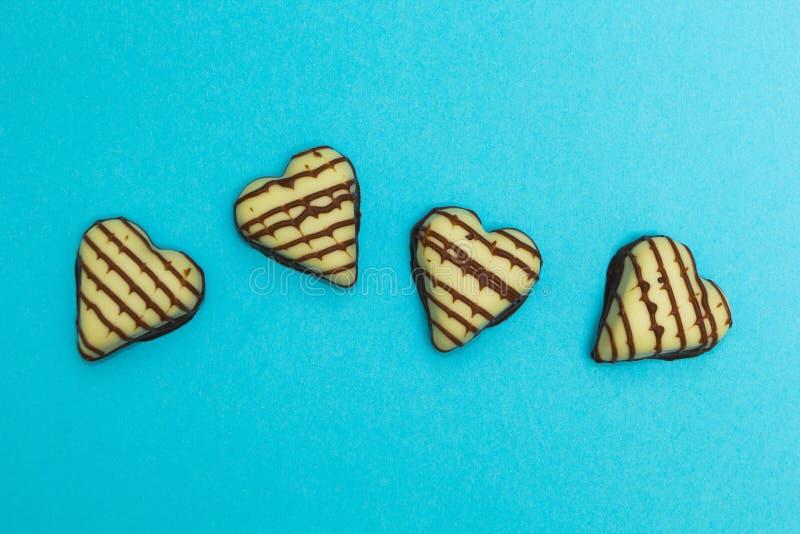 Czekoladowy cukierek w formie serca odizolowywającego na błękitnym tle fotografia stock