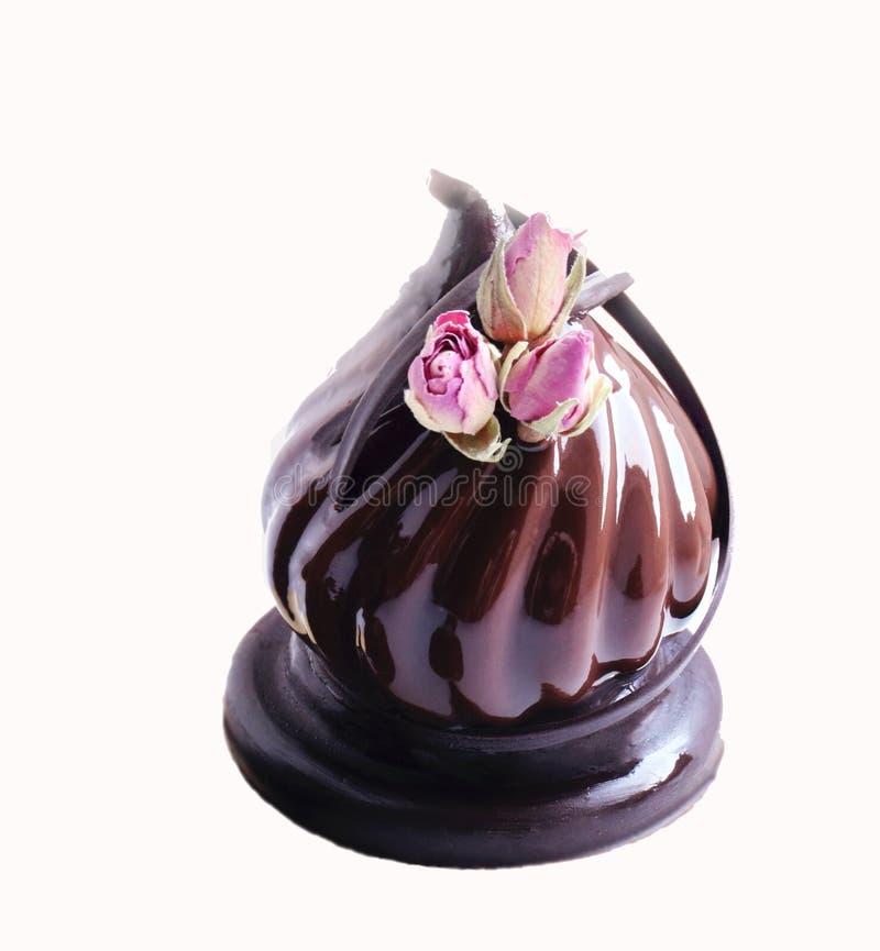Czekoladowy deser z wysuszonymi różami i czekoladowa dekoracja na białym tła cięciu obraz royalty free