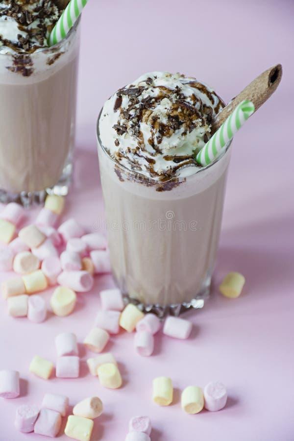 Czekoladowy milkshake z lody i batożącą śmietanką, marshmallows, ciastka, gofry, słuzyć w szklanej filiżance Lekki t?o zdjęcie royalty free