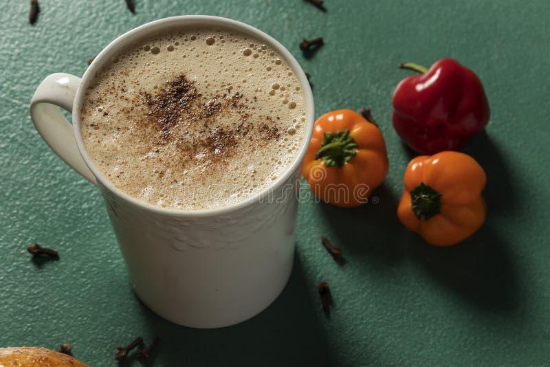 Czekoladowy napój towarzyszący pieprzami w białym filiżanki i zieleni tle zdjęcia royalty free