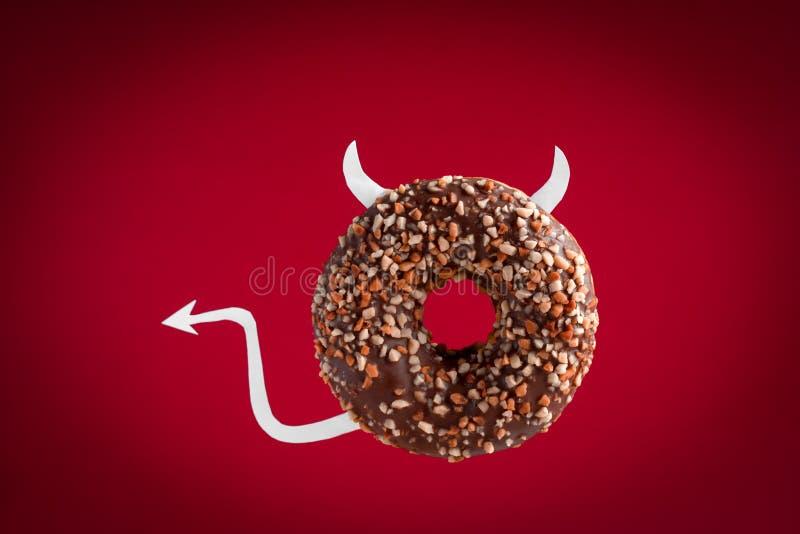 czekoladowy pączek z papieru ogonu i rogów lataniem na czerwonym tle fotografia stock