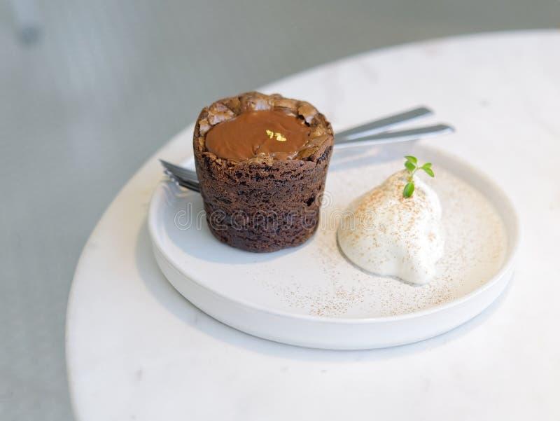 Czekoladowy punkt lawy tort słuzyć z bat śmietanką na białym round talerzu obrazy stock