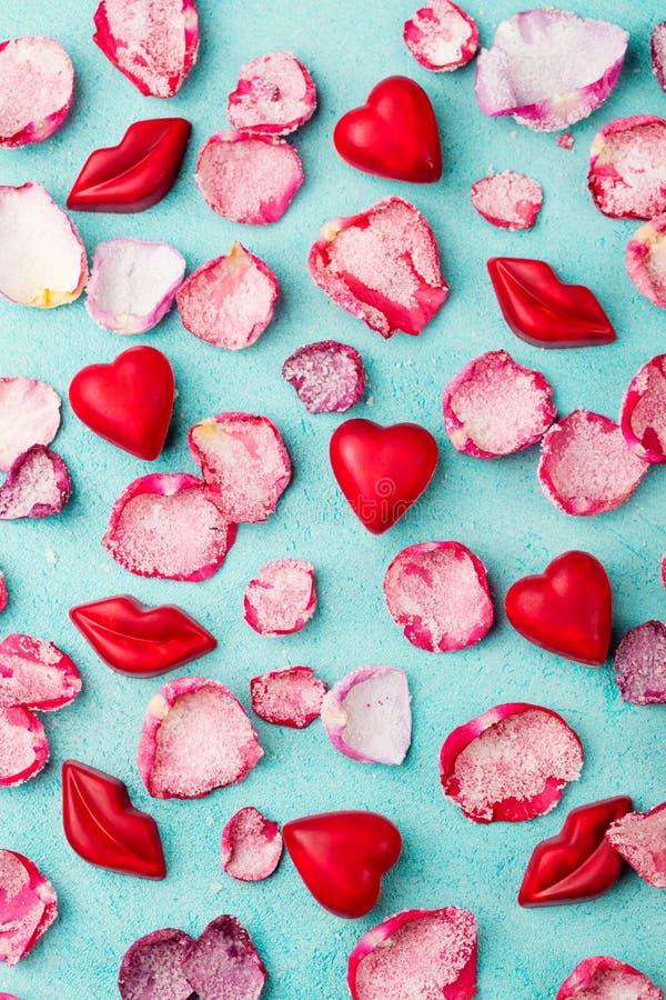 Czekoladowy serce i wargi kształtowaliśmy cukierki z róża candied osłodzonymi płatkami niebieska tła Odgórny widok obraz royalty free