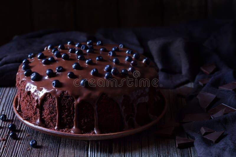 Czekoladowy tort dekorował z czernicami na rocznika drewnianym stołowym tle obraz stock