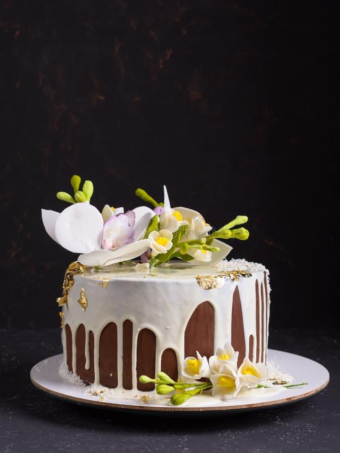 Czekoladowy tort dekorował z kwiatami i nalewał białego lodowacenie na czerń kamienia tle obrazy stock