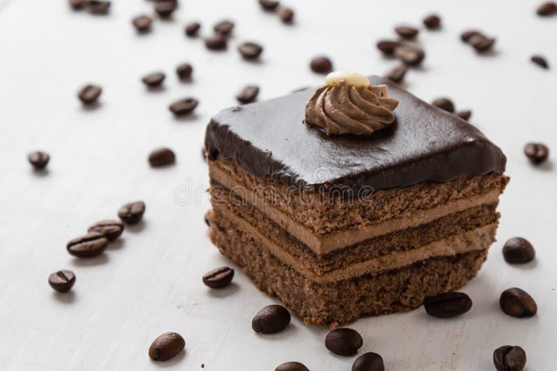Czekoladowy tort i kawowe fasole na stole obrazy royalty free