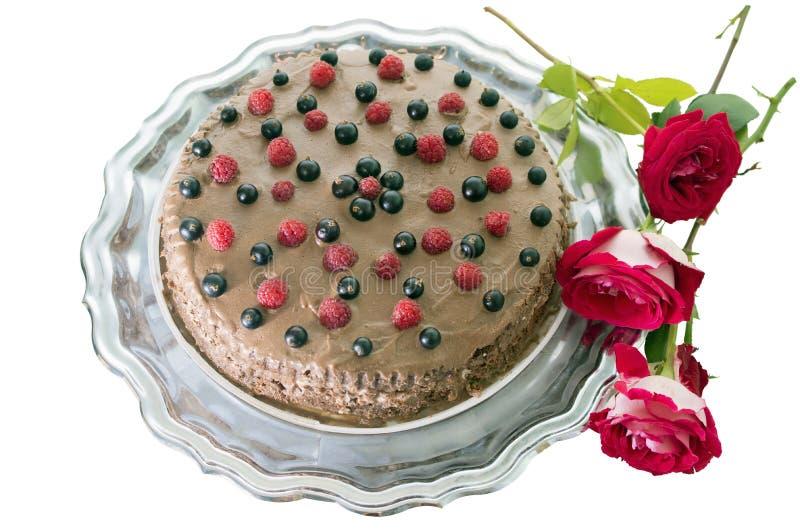 Czekoladowy tort z świeżymi jagodami i różami odizolowywającymi, obrazy royalty free