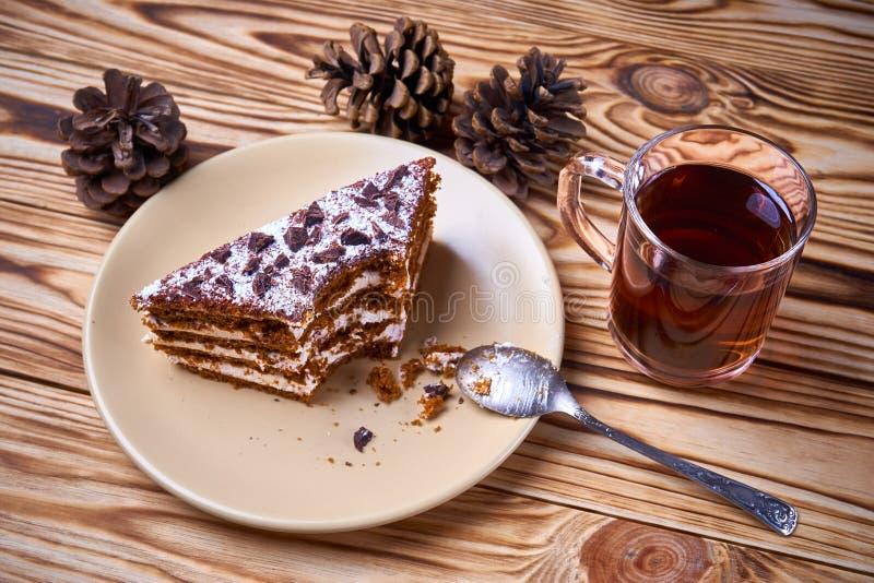 Czekoladowy tort z rżniętym kawałkiem na talerzu, filiżanka gorąca czarna herbata zdjęcia stock