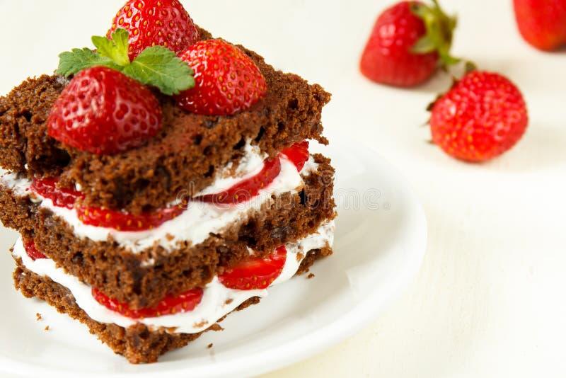 Czekoladowy tort z truskawką i śmietanką fotografia stock