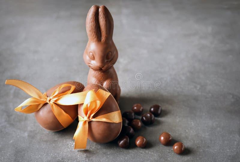Czekoladowy Wielkanocny królik, jajka i cukierki na stole, obraz stock