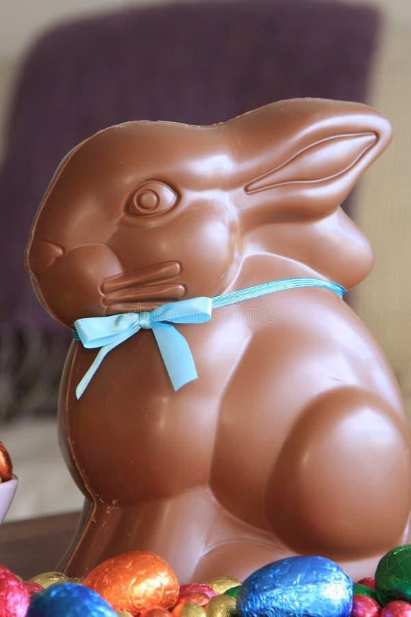 Czekoladowy Wielkanocny królik siedzi wśród czekoladowych jajek obraz stock