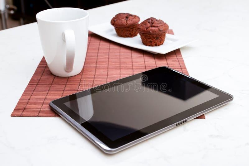 Czekoladowych układów scalonych Muffins z filiżanką kawy i pastylka pecetem obraz royalty free