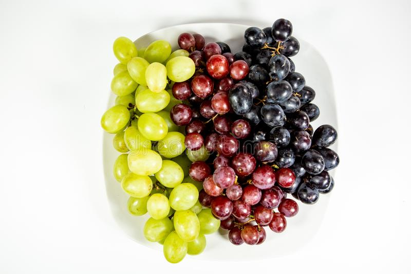 Czerń, czerwień, zieleni beznasienni winogrona w głębokim białym pucharze obrazy stock