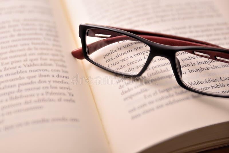 Czerń i czerwoni czytelniczy szkła na otwartej książce obrazy stock