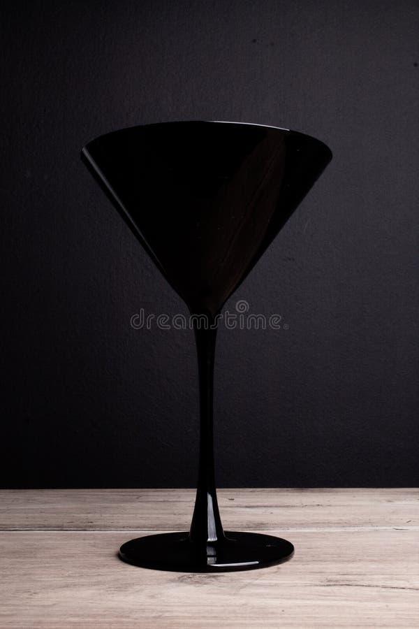 Czerń na czerni: jeden elegancki tylny szklany Martini szkło na czarnym t obraz stock