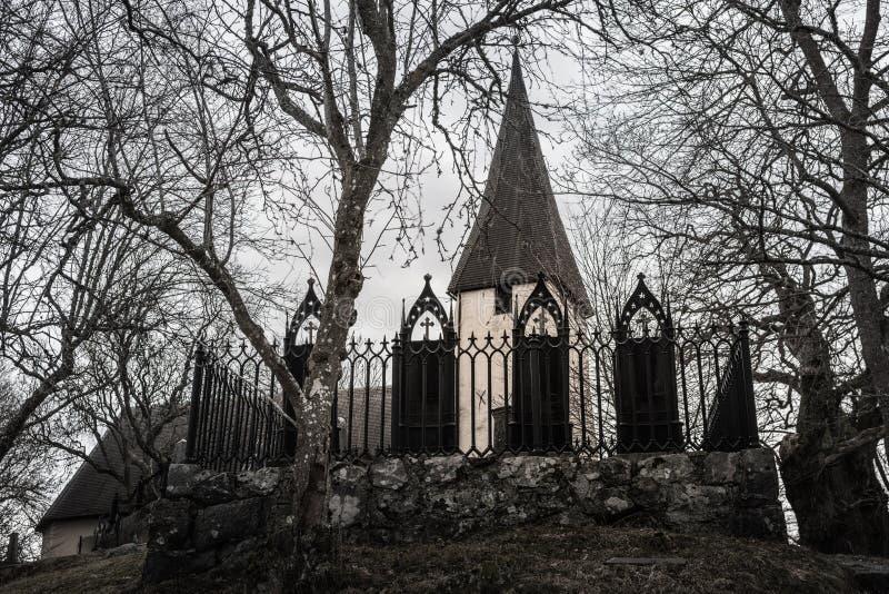 Czerń ornamentował żelaznych gravestones z stary kościelny wierza w tle obrazy stock