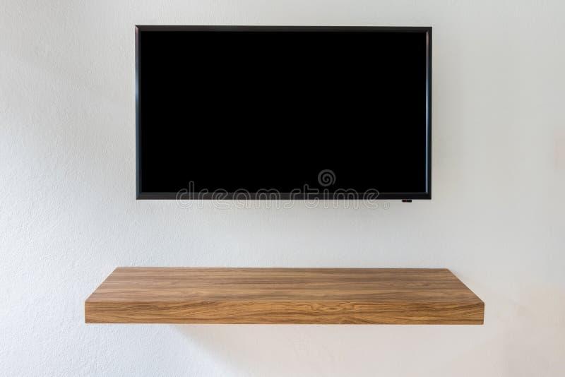 Czerń PROWADZIŁ tv telewizi ekran na biel ściany tle z nowożytnym drewnianym stołem obraz stock