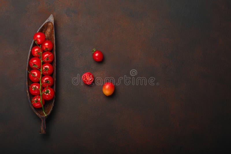Czereśniowi pomidory kapują na drewnianym postaci półkowym i ośniedziałym brązu tle zdjęcie stock