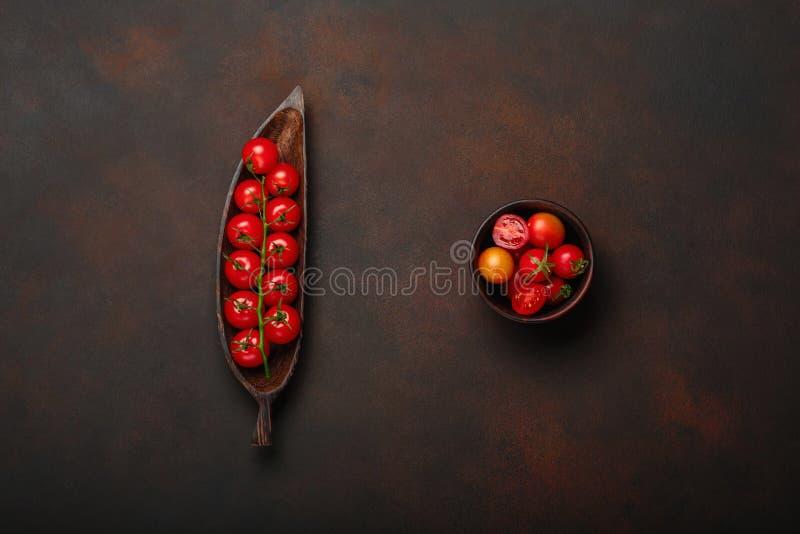 Czereśniowi pomidory kapują na drewnianym postaci półkowym i ośniedziałym brązu tle zdjęcie royalty free