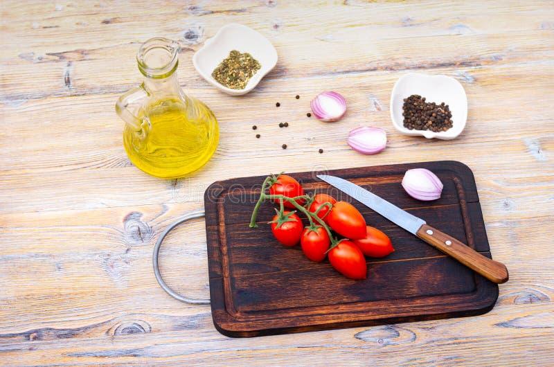 Czereśniowi pomidory na gałąź, jarzynowym oleju i pikantność na drewnianym tle, odgórny widok zdjęcia stock
