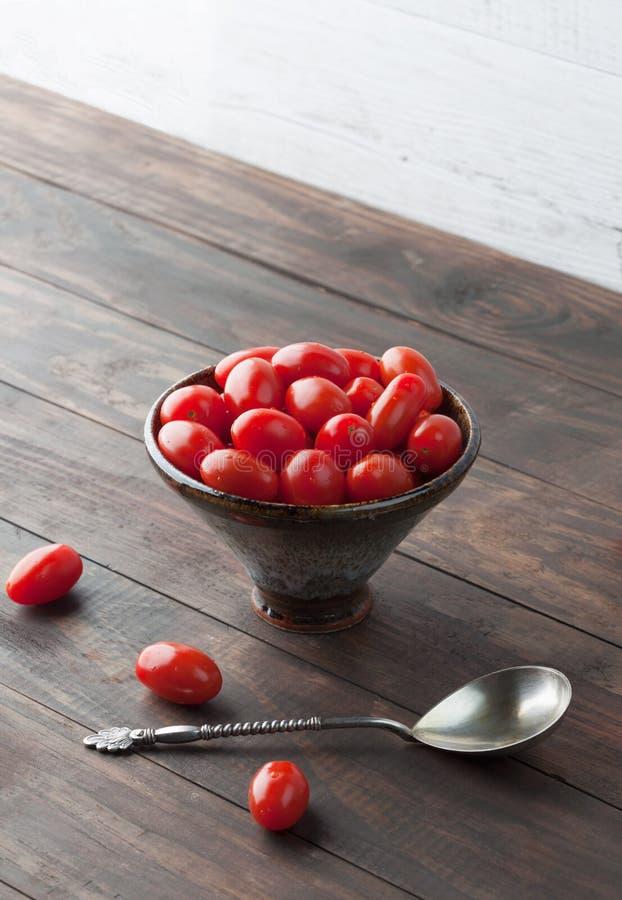 Czereśniowi pomidory w ceramicznym pucharze Pionowo wizerunek z kopii przestrzenią zdjęcie royalty free