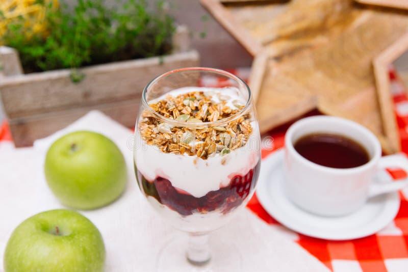Czereśniowy jogurtu parfait z crispy filiżanką herbata i granola obraz royalty free