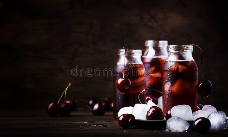 Czereśniowy napój, zimny sok z lodem w butelkach na rocznika drewnianym stole, lato owocowy koktajl fotografia royalty free