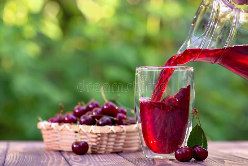 Czereśniowy soku dolewanie w szkło fotografia stock