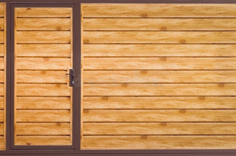 Czerep drewnianego brązu nowożytny ogrodzenie z wejściowym drzwi, zbliżenie Frontowy widok r Kopia fotografia stock