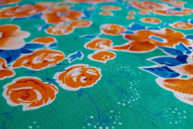 Czerep jaskrawy trawy zieleni rocznika tkaniny kolorowy wzór z dużą pomarańcze kwitnie pożytecznie jako tła lub tkaniny próbka zdjęcia stock