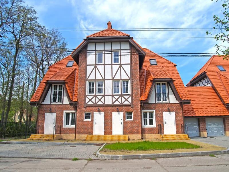Czerep nowy dom miejski pod czerwonym dachówkowym dachem zdjęcia royalty free