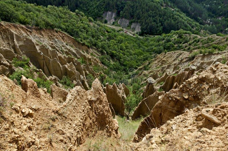 Czerep sławni Stob ostrosłupy z niezwykłą kształt czerwienią, żółtymi rockowymi formacje, zieleni krzaki i drzewa, wokoło obraz stock