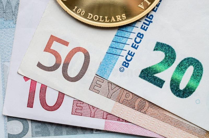 Czerep złocista moneta z wartością nominalną 100 dolarów na tle Euro banknoty obrazy stock