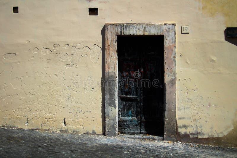 Czerni burnt drzwi, kontrastuje z nim ` s palu brzoskwini ściany i starzejącą się ramę w Rzym Włochy, zdjęcie royalty free