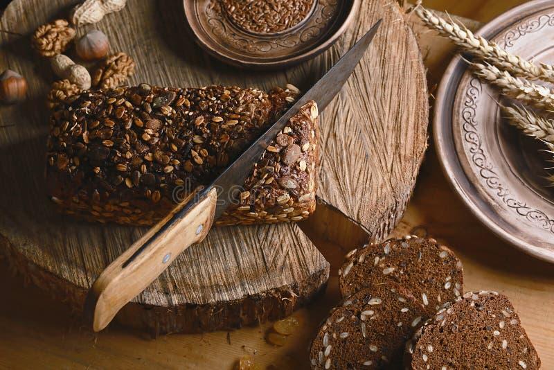 Czerni pokrojonego chleb na desce, rocznika nóż, banatka krótkopędy, lna ziarno, niż przecinanie chleb na stole o i drewnianym tl fotografia royalty free