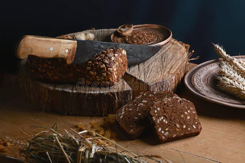 Czerni pokrojonego chleb na desce, rocznika nóż, banatka krótkopędy, lna ziarno, niż przecinanie chleb na stole o i drewnianym tl zdjęcie stock