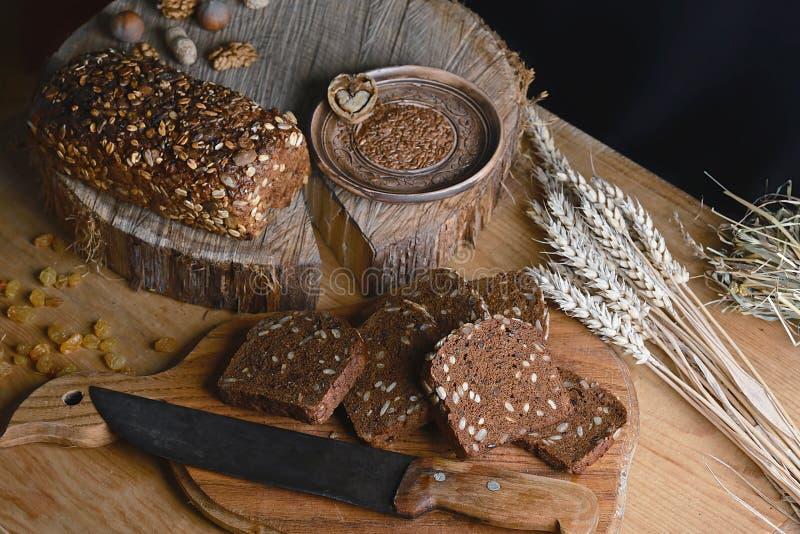 Czerni pokrojonego chleb na desce, rocznika nóż, banatka krótkopędy, lna ziarno na stole i drewnianym tle na fiszorku, pojęcie obraz royalty free