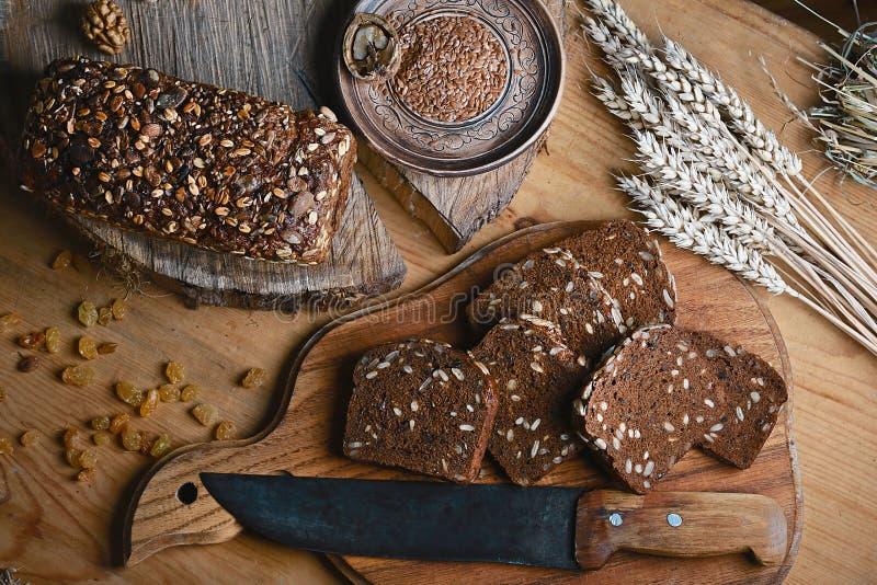 Czerni pokrojonego chleb na desce, rocznika nóż, banatka krótkopędy, lna ziarno na stole i drewnianym tle na fiszorku, pojęcie zdjęcia royalty free