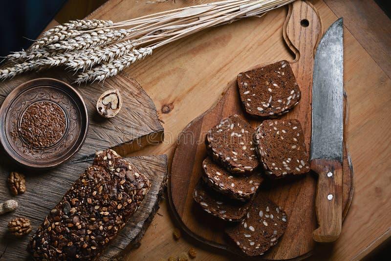 Czerni pokrojonego chleb na desce, rocznika nóż, banatka krótkopędy na stole i drewnianym tle na fiszorku, pojęcie zdrowy zdjęcie royalty free